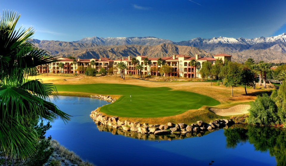 A fairway and green against a backdrop of mountains