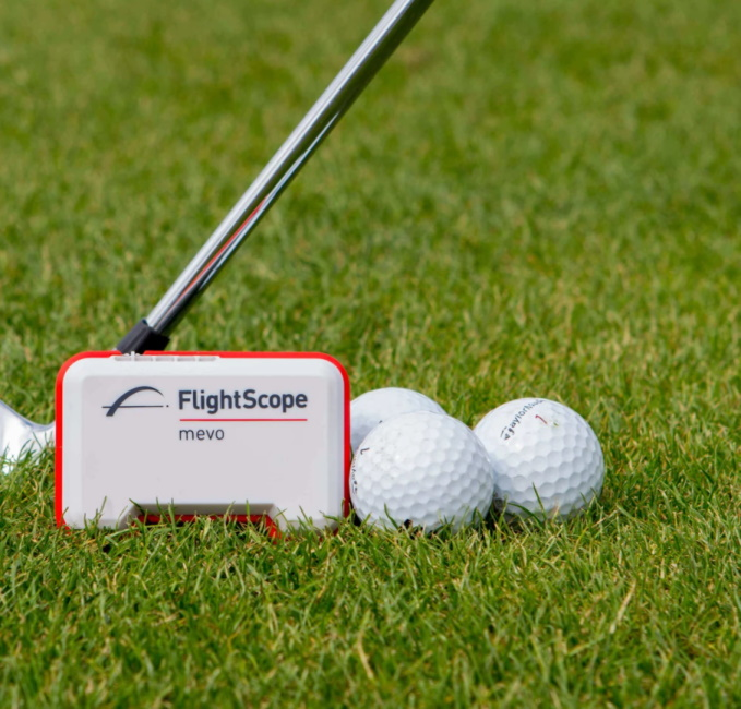 FlightScope Mevo Launch Monitor with balls and a club